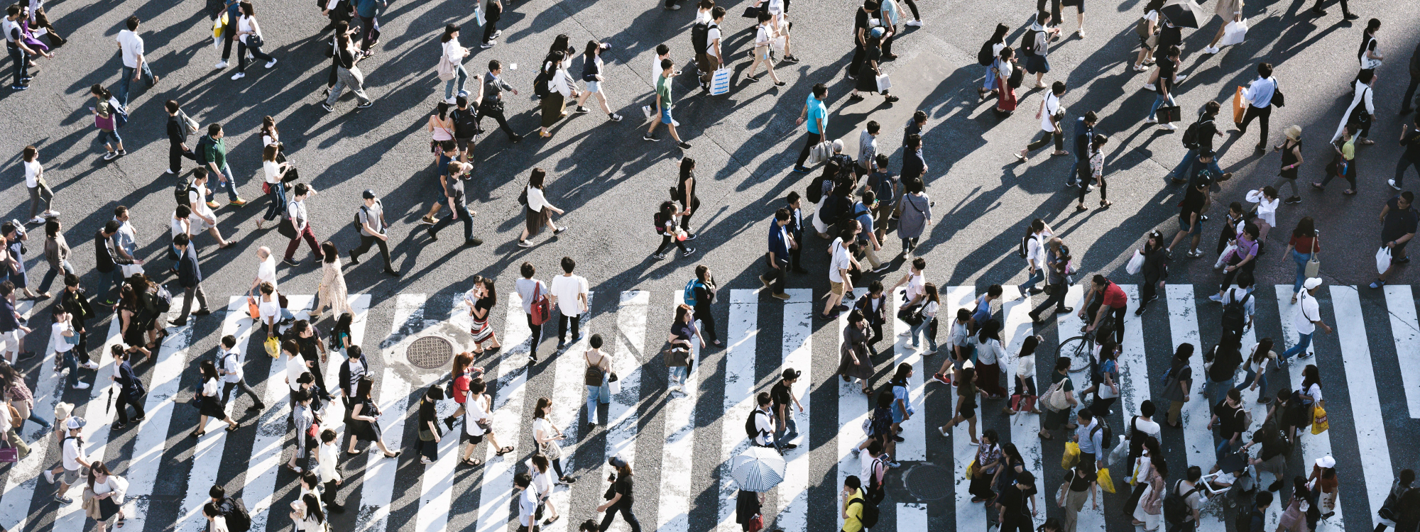 Menschen überqueren in Massen einen Zebrastreifen
